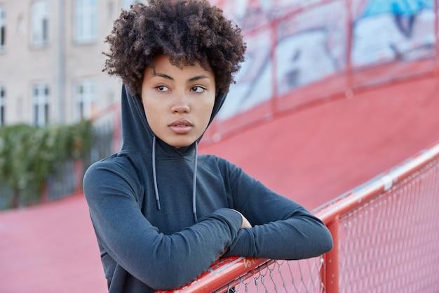 Nadenkend sportieve vrouw poseren in buitenomgeving