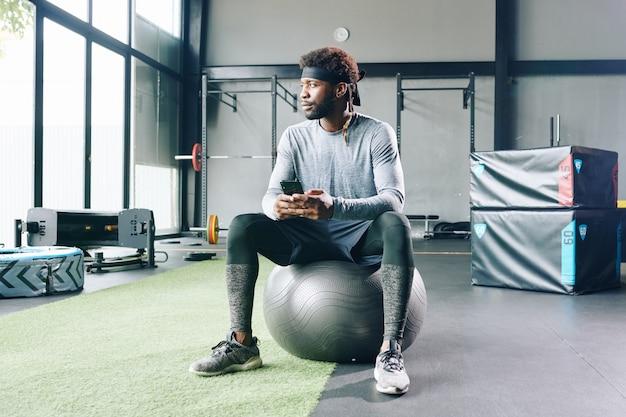 Nadenkend sportman zitten van fitness bal