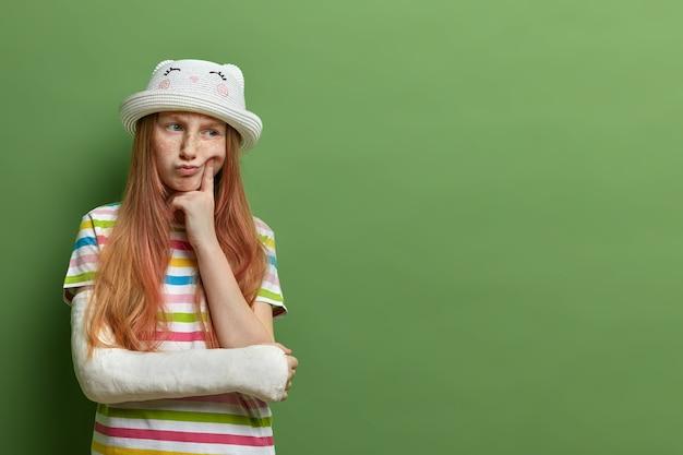 Nadenkend sproeterig meisje met rood haar, houdt de vinger op de wang, heeft een ontevreden uitdrukking, heeft een arm gebroken, kan niet met kinderen buiten spelen, geïsoleerd op groene muur, lege ruimte voor promo