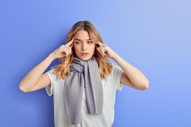 Nadenkend tienermeisje concentreerde zich op gedachten die op blauwe muur worden geïsoleerd
