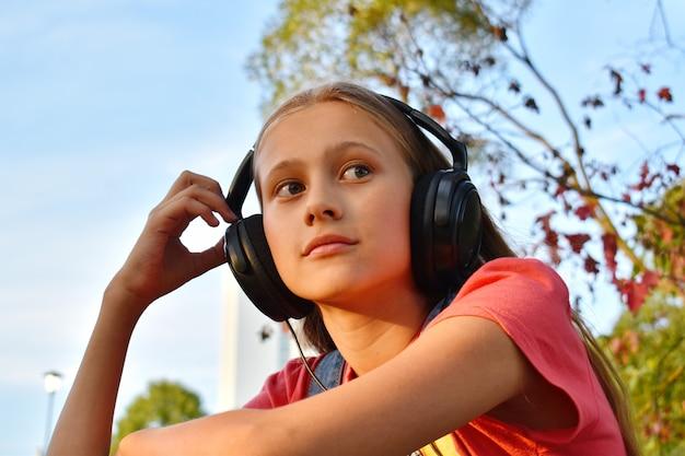 Nadenkend tienermeisje die in hoofdtelefoons aan muziek luisteren outsite.