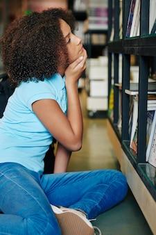 Nadenkend tienermeisje kijken naar boeken op planken in bibliotheek