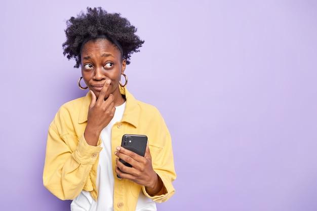 Nadenkend tienermeisje met donkere huid met gekamd krullend haar maakt gebruik van moderne mobiele telefoon chatten gefocust weg heeft doordachte uitdrukking draagt gele jas geïsoleerd op paars