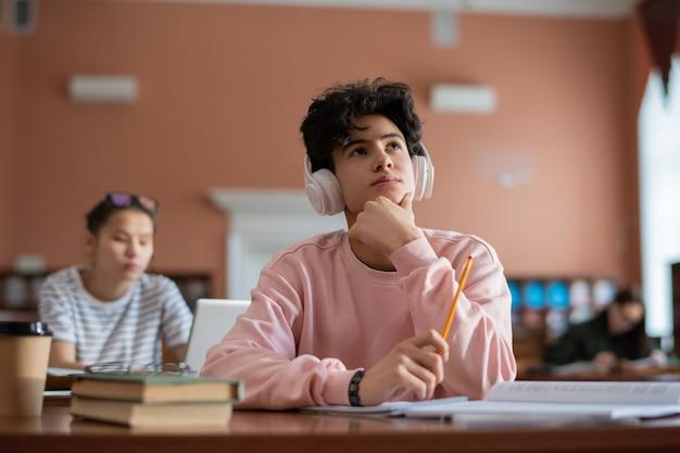 Nadenkend tienerstudent in hoofdtelefoons en vrijetijdskleding die door bureau in universiteitsbibliotheek zitten en voor seminarie voorbereiden