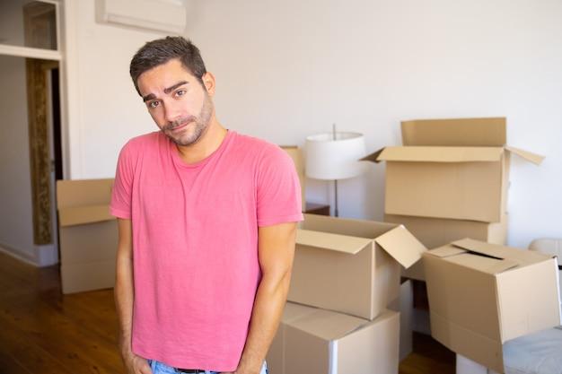 Nadenkend verbaasd jongeman verhuizen in nieuw appartement, staande voor hoop geopende kartonnen dozen, camera kijken
