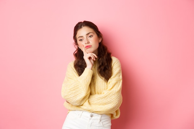 Nadenkend verdrietig meisje dat opzij kijkt, uit elkaar gaat, denkt wat te doen, humeurig en boos tegen de roze muur staat.