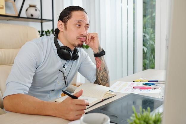Nadenkend verveeld grafisch ontwerper leest briefing van klant en bedenkt wat hij moet tekenen