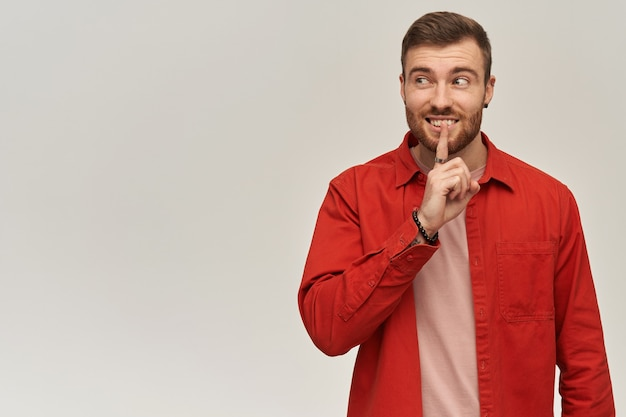 Nadenkend verwarde jonge bebaarde man in rood overhemd met stilte gebaar en opzij kijkend over witte muur