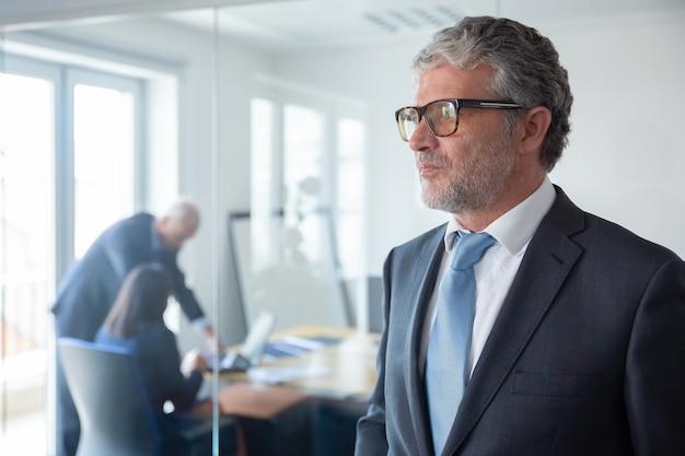 Nadenkend volwassen zakenman in formeel pak en glazen staan door de glazen wand van het kantoor, wegkijken. kopieer ruimte. portret bedrijfsconcept