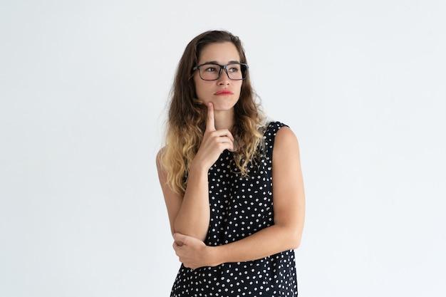 Nadenkend vrij jonge vrouw kin aanraken met vinger en wegkijken.