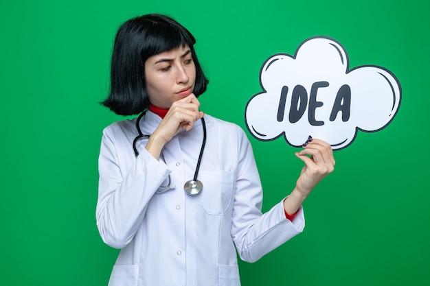 Nadenkend, vrij kaukasisch meisje in doktersuniform met een stethoscoop die de ideebel vasthoudt en bekijkt