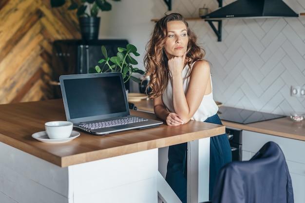 Nadenkend vrouw in de keuken aan de tafel met een laptop.