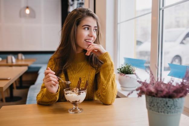 Nadenkend vrouw in gebreide trui raam kijken tijdens rust in café in koude dag. indoor portret van romantische vrouw in geel overhemd genieten van koffie in restaurant.