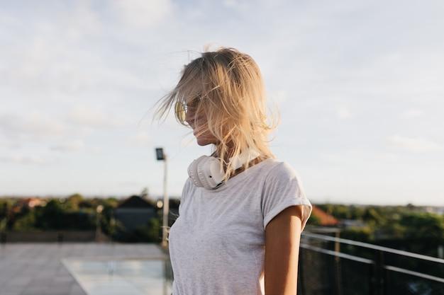 Nadenkend vrouw in wit t-shirt wegkijken tijdens een wandeling door de stad in de avond. stijlvolle blonde meisje in koptelefoon poseren op hemelachtergrond.