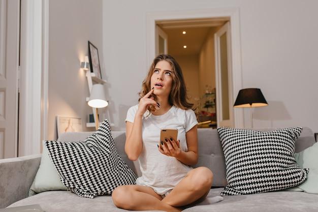 Nadenkend vrouw in wit t-shirt zitten met gekruiste benen en opzoeken