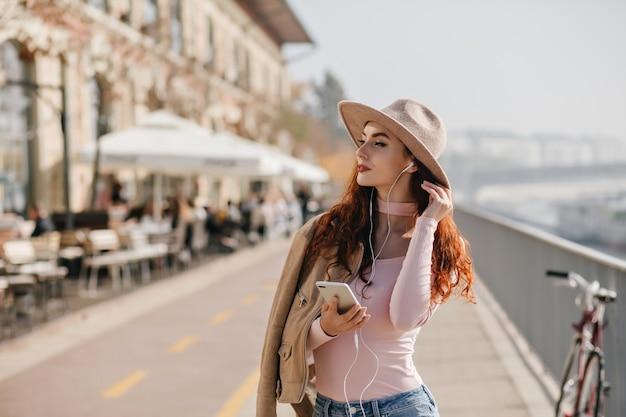 Nadenkend vrouw luisteren muziek in oortelefoons en genieten van uitzicht op de stad