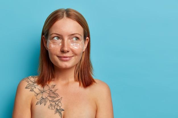 Nadenkend vrouw met sproeten met natuurlijk rood haar, staat shirtloos, kijkt opzij en denkt aan iets plezierigs, draagt transparante vlekken om wallen te verminderen, geïsoleerd op een blauwe muur