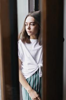 Nadenkend vrouwelijk model met rechte kapsel ontspannen thuis in weekendochtend. aantrekkelijke brunette vrouw in pyjama wegkijken.