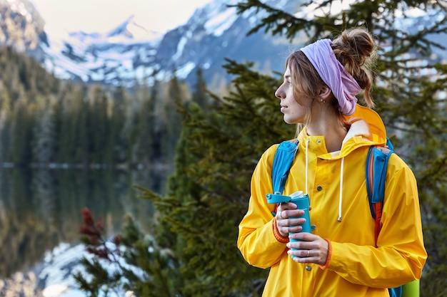 Nadenkend vrouwelijke bergbeklimmer draagt sjaal om hoofd, gele regenjas, geniet van hete koffie uit kolf