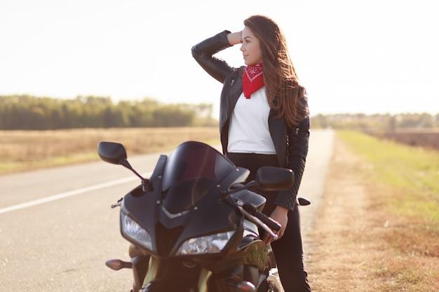 Nadenkend vrouwelijke bestuurder in stijlvolle kleding, poses op snelle motor, kijkt bedachtzaam opzij