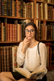 Nadenkend vrouwelijke student zitten met boek in de bibliotheek