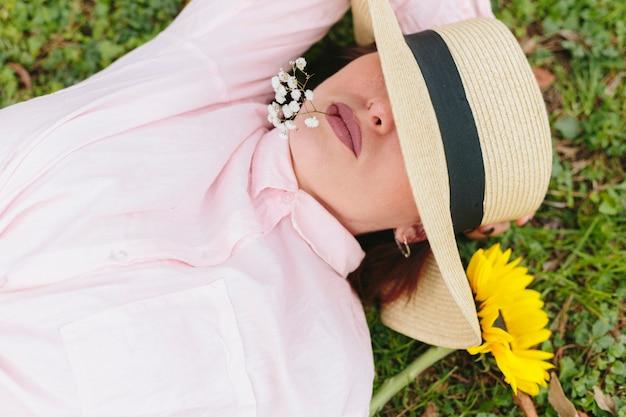 Nadenkend wijfje in hoed die op gras ligt