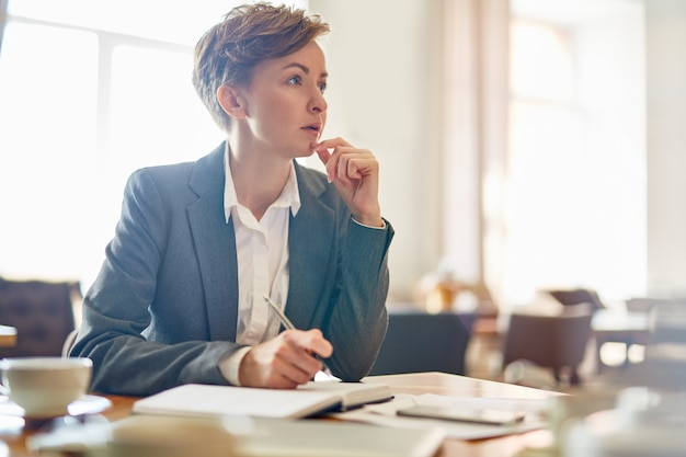 Nadenkend zakenvrouw in koffiehuis