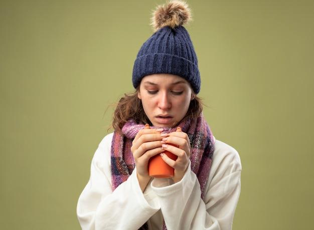 Nadenkend ziek meisje dragen witte mantel en muts met sjaal houden en kijken naar kopje thee geïsoleerd op olijfgroen