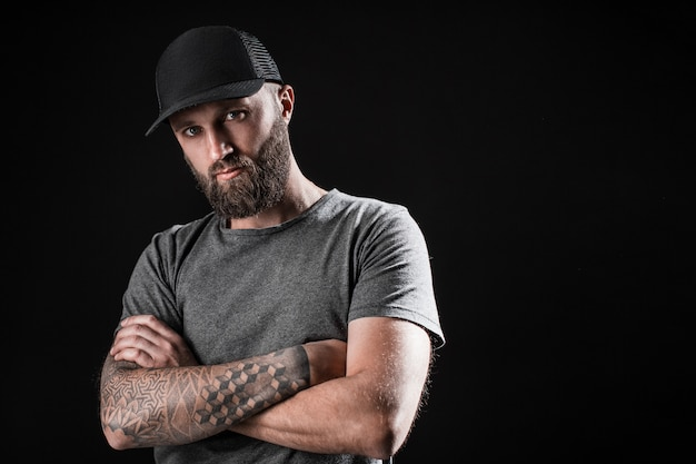 Nadenkend zwart bebaarde man gekleed in een grijs shirt, zonnebril en baseball cap.