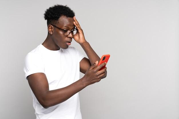 Nadenkend zwarte man hoofd krabben kijken naar plannen van mobiele telefoon denken