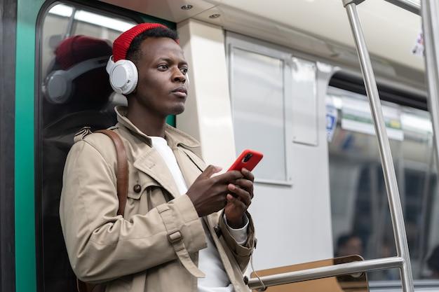 Nadenkend zwarte man in metro denken met behulp van mobiele telefoon luistert naar muziek met draadloze koptelefoon