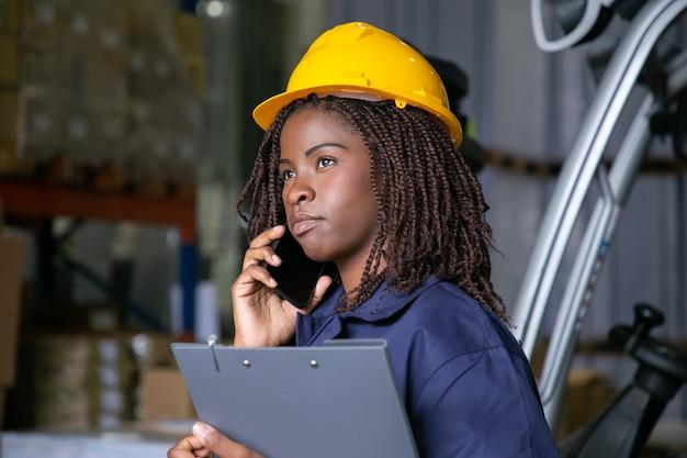Nadenkend zwarte vrouwelijke ingenieur in veiligheidshelm staande in magazijn en praten over mobiel. planken met goederen op achtergrond. kopieer ruimte. arbeids- of communicatieconcept