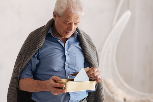 Nadenkende, aardige oude man die naar de doos met brieven kijkt en een envelop vasthoudt terwijl hij zich zijn verleden herinnert