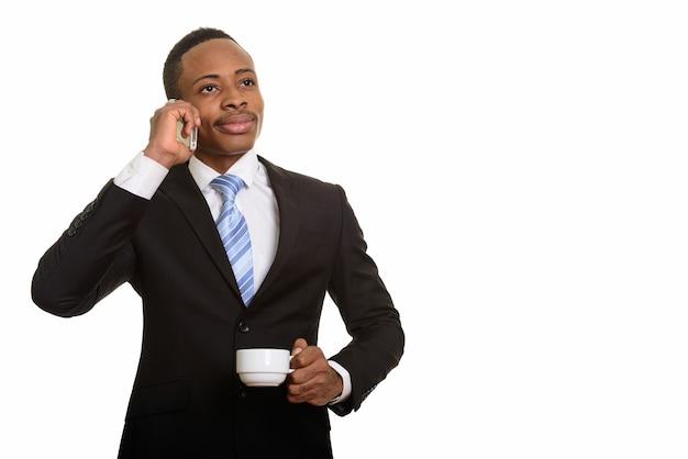 Nadenkende afrikaanse zakenman die op mobiele telefoon spreekt