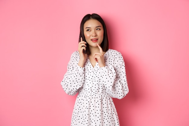 Nadenkende aziatische vrouw die mobiele telefoon roept om orde te maken, nadenkt en opzij kijkt, die zich tegen roze bevindt.