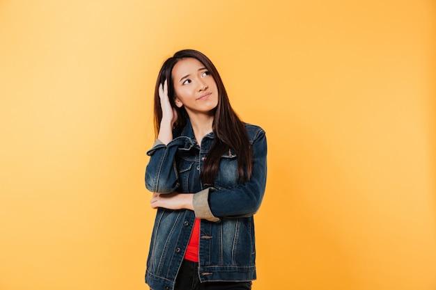 Nadenkende aziatische vrouw in jasje die hoofd houden en weg kijken