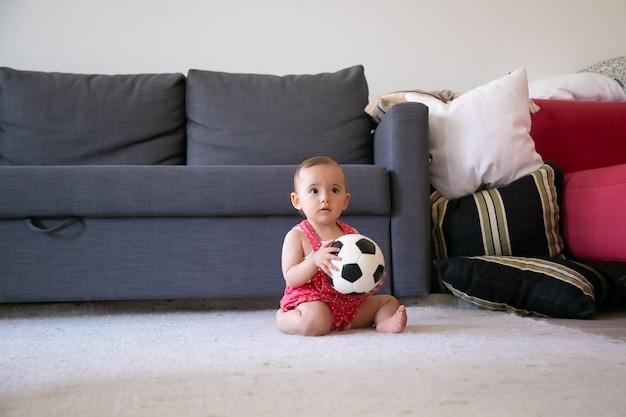 Nadenkende babymeisje bedrijf voetbal, zittend op een tapijt op blote voeten en wegkijken. mooie peuter in rode tuinbroek korte broek spelen thuis in de buurt van bank. vakantie-, weekend- en jeugdconcept