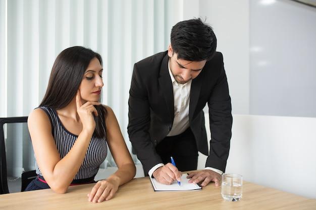 Nadenkende bedrijfsdame die aan collega'sidee op vergadering luisteren