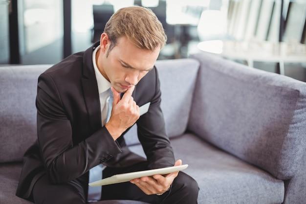 Nadenkende bedrijfsmens die digitale tablet bekijken