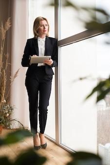 Nadenkende bedrijfsvrouw die tablet gebruikt