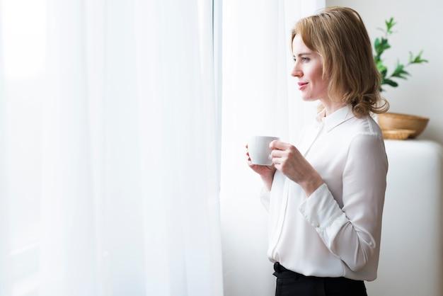 Nadenkende bedrijfsvrouw met koffiekop