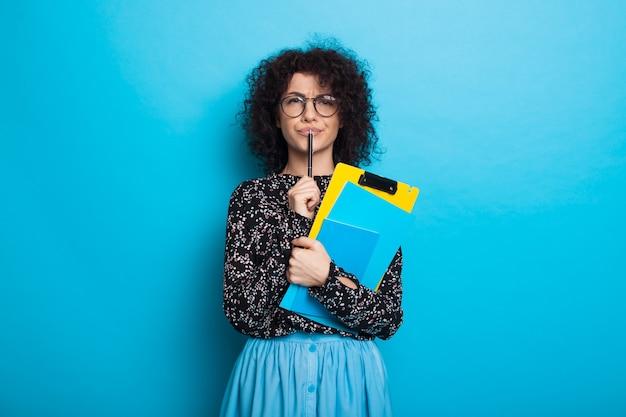 Nadenkende blanke student met krullend haar poseren met een boek dat een jurk op een blauwe muur draagt