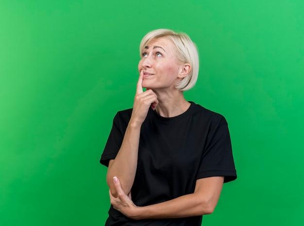 Nadenkende blonde slavische vrouw van middelbare leeftijd die de vinger op de lippen zet die de elleboog houdt omhoog geïsoleerd op groene achtergrond met exemplaarruimte kijkt