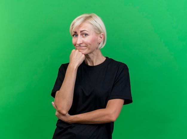 Nadenkende blonde slavische vrouw van middelbare leeftijd die hand op kin zet die voorzijde bekijkt die op groene muur met exemplaarruimte wordt geïsoleerd
