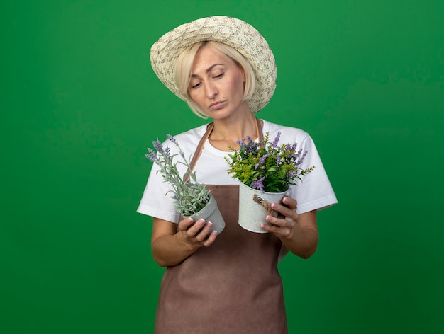 Nadenkende blonde tuinmanvrouw van middelbare leeftijd in uniform die hoed draagt en naar bloempotten kijkt die op groene muur met exemplaarruimte worden geïsoleerd