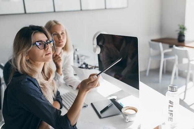 Nadenkende blonde vrouw die in glazen potlood houdt en weg kijkt tijdens werk in bureau. indoor portret van drukke langharige vrouwelijke accountant met behulp van computer.