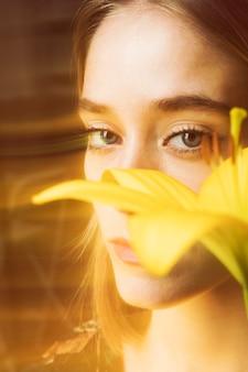 Nadenkende blonde vrouw met gele bloem