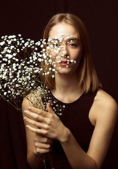 Nadenkende blonde vrouw met witte bloemen