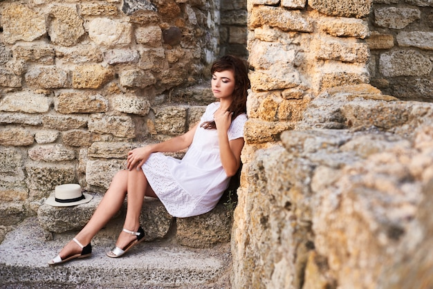 Nadenkende boerin die op de treden zit en haar haar houdt. Premium Foto