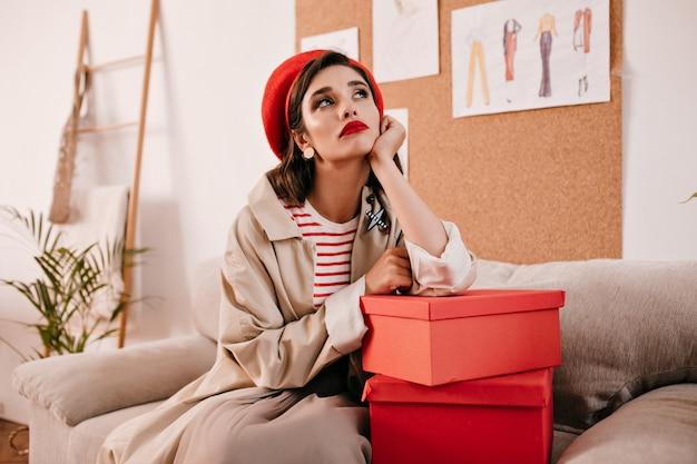Nadenkende dromerige vrouw poseren in de kamer en leunend op geschenkdoos. nadenkend dame in stijlvolle rode baret en lange beige jas zit op de bank.